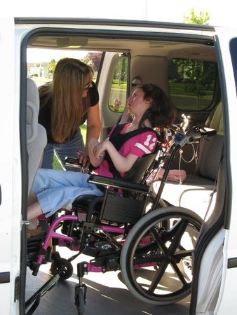 Mother securing her daughter in a new adapted van.